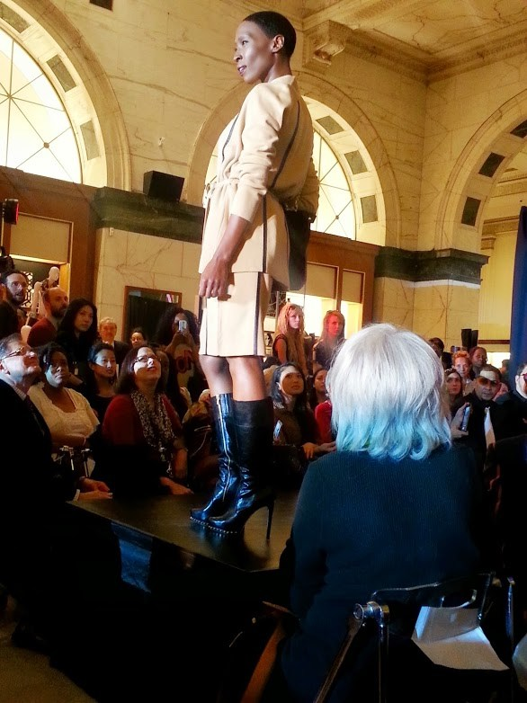 Philadelphia Fashion Incubator model wearing a tan faux leather trimmed skirt suit that with tall heeled boots.  Photo Credit: Bianca Dorville