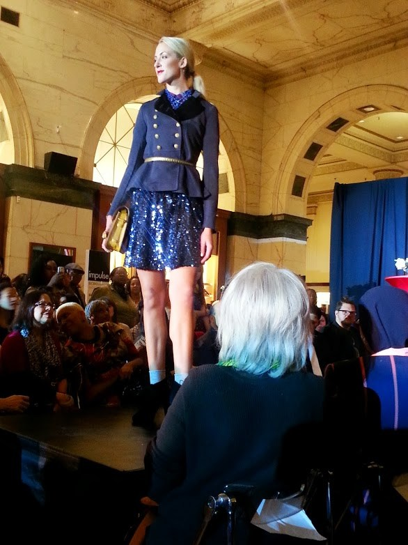 Philadelphia Fashion Incubator model wearing a blue sequin skirt with a flared military inspired pea coat.  Photo Credit: Bianca Dorville